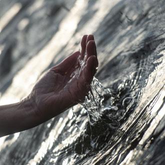 viser hånd der øser vand op fra havet