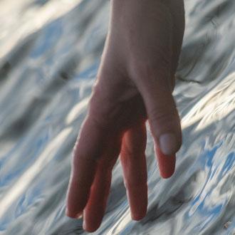 viser hånd der rækker ned til havet